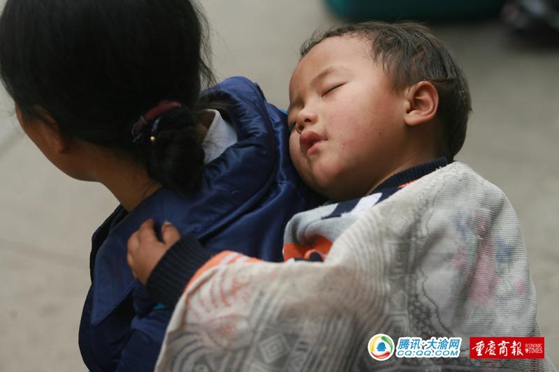 一名小朋友在家人的背上睡着了 记者 刘嵩 摄