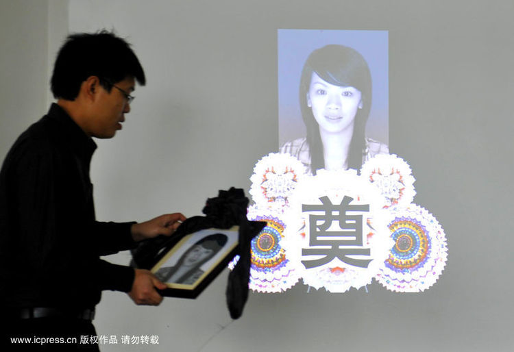 2010年2月4日,福建漳州殡仪馆,庄华贵拿着妻子的遗像照片。