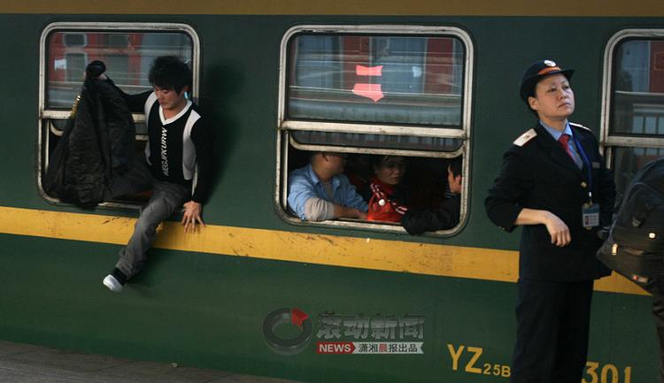 一名已经上了车放好行李的乘客,忍受不了绿皮车里的拥堵和混乱的环境,爬出车窗来呼吸上车前的最后一缕新鲜空气。