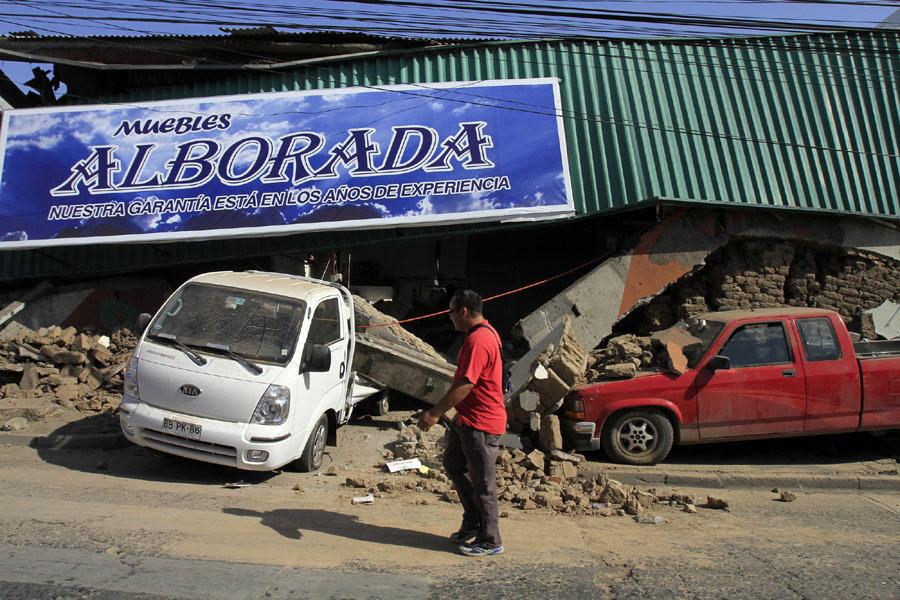 2月27日,在智利塔尔卡省,两辆汽车被在地震中坍塌的房屋损坏。