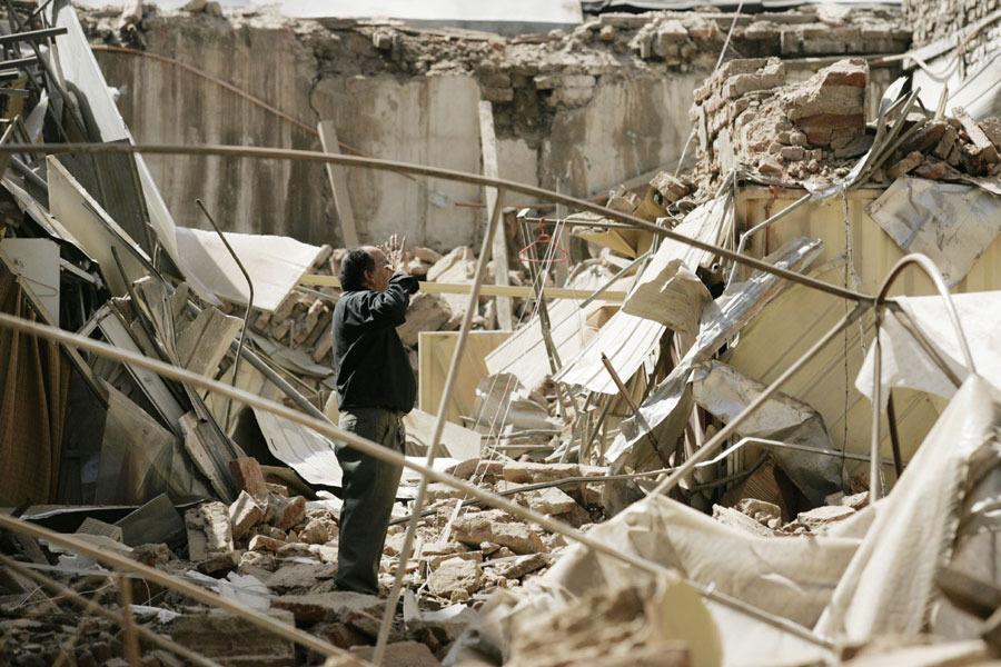 2月27日,在智利首都圣地亚哥,一名男子站在一片楼房坍塌后的废墟中。