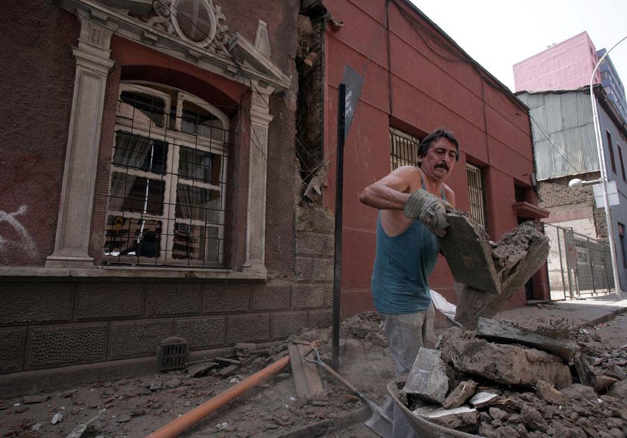 2月27日,在智利首都圣地亚哥,一名男子清理地震后的瓦砾。