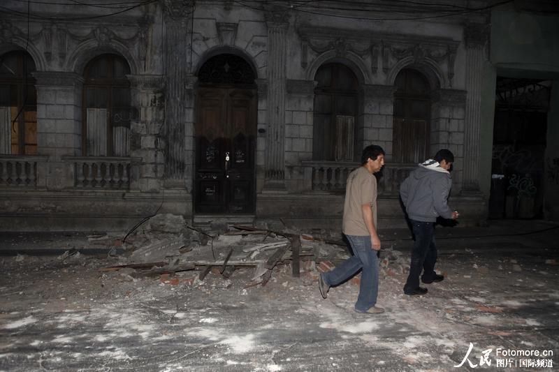 2010年2月27日,智利,塔尔卡:当地民众走在地震废墟上。智利中部康塞普西翁省附近北京时间2010年2月27日14时34分发生里氏8.8级强烈地震,智利首都圣地亚哥有震感。