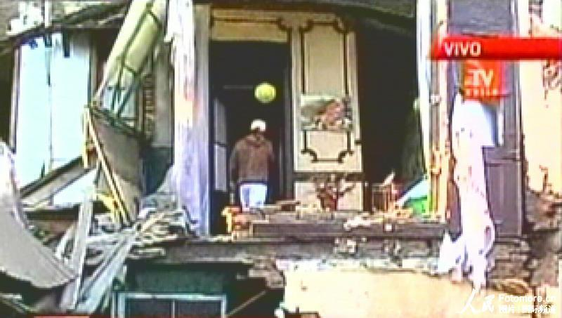 2010年2月27日,智利,塔尔卡:一位居民站在毁坏的楼房中。智利中部康塞普西翁省附近北京时间2010年2月27日14时34分发生里氏8.8级强烈地震,智利首都圣地亚哥有震感。