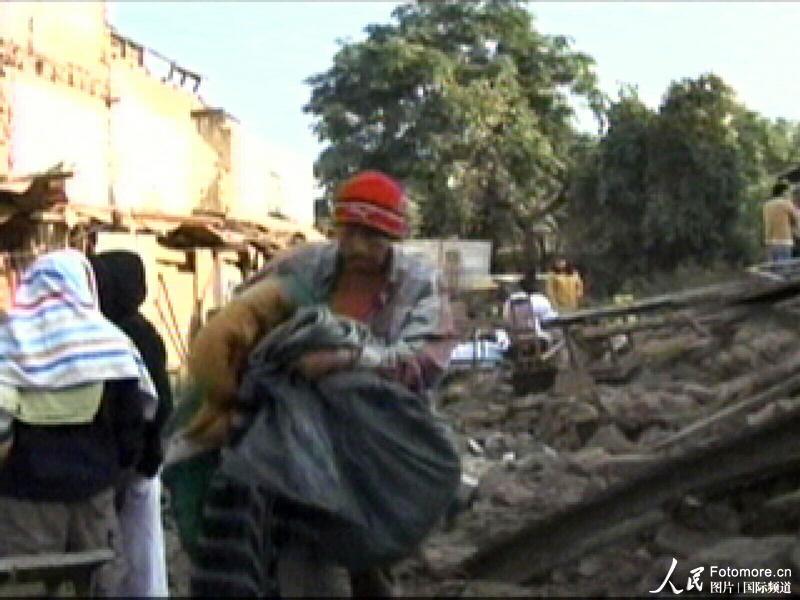 2010年2月27日,智利,塔尔卡:人们从地震废墟上走过。智利中部康塞普西翁省附近北京时间2010年2月27日14时34分发生里氏8.8级强烈地震,智利首都圣地亚哥有震感。