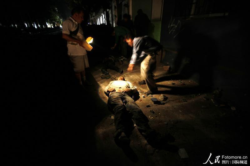 2010年2月27日,智利,塔尔卡:人民看着地震遇难者。智利中部康塞普西翁省附近北京时间2010年2月27日14时34分发生里氏8.8级强烈地震,智利首都圣地亚哥有震感。