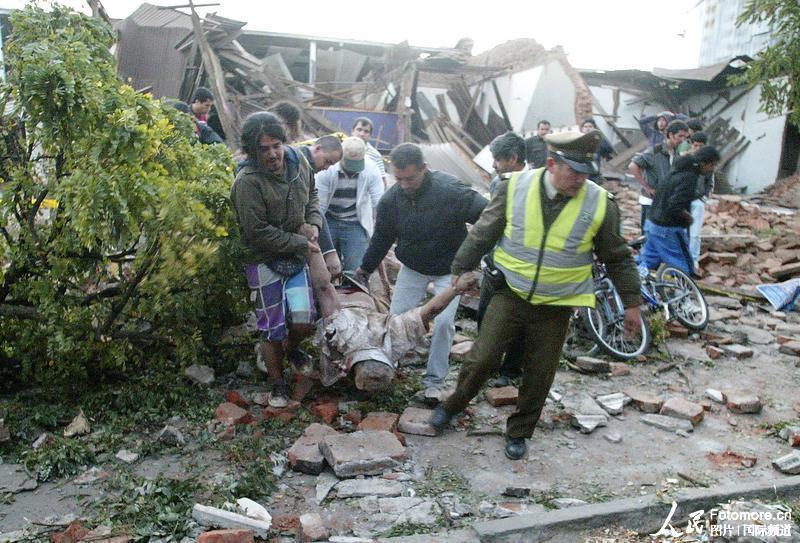 2010年2月27日,智利,塔尔卡:警察和当地的居民从废墟中抬出一位地震伤员。