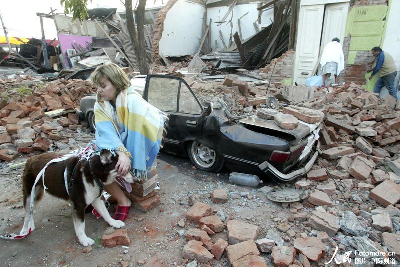 2010年2月27日,智利,塔尔卡:一位妇女坐在因地震而损坏的房屋前。智利中部康塞普西翁省附近北京时间2010年2月27日14时34分发生里氏8.8级强烈地震,智利首都圣地亚哥有震感。