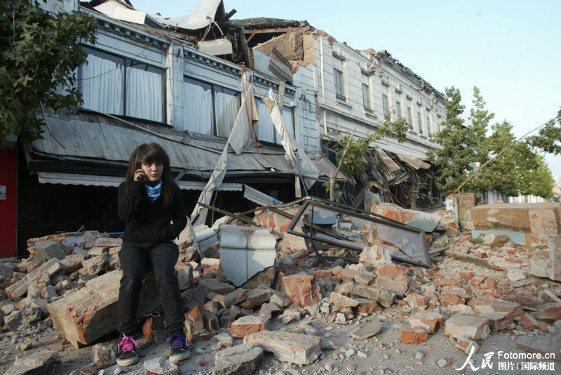 2010年2月27日,智利,塔尔卡:一为居民坐在因地震倒塌的房屋废墟上。智利中部康塞普西翁省附近北京时间2010年2月27日14时34分发生里氏8.8级强烈地震,智利首都圣地亚哥有震感。