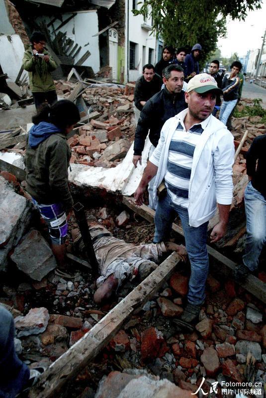 2010年2月27日,智利,塔尔卡:人们站在一位地震遇难者旁边。智利中部康塞普西翁省附近北京时间2010年2月27日14时34分发生里氏8.8级强烈地震,智利首都圣地亚哥有震感。