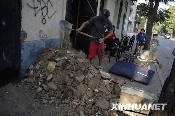 2月27日,在智利首都圣地亚哥,人们在地震发生后清理屋前的建筑碎片。新华社发(维克多·罗哈斯摄)