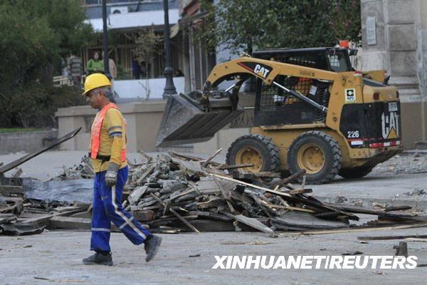 2月27日,在智利首都圣地亚哥,市政工人清理地震发生后散落在街道上的建筑碎片。