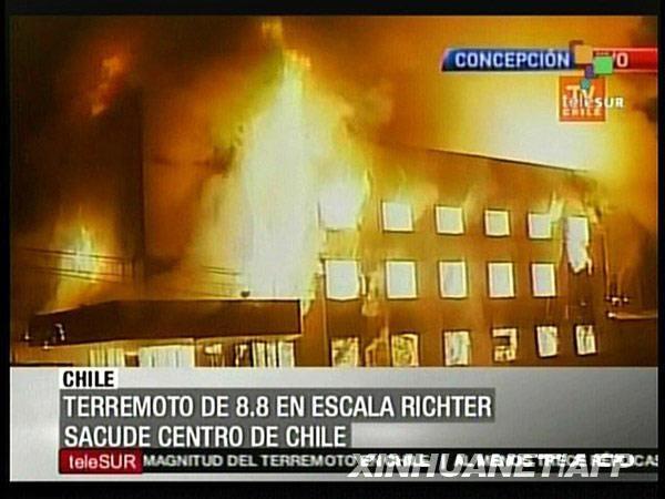这张2月27日的电视截图显示,在智利康塞普西翁,一幢建筑在地震后起火燃烧