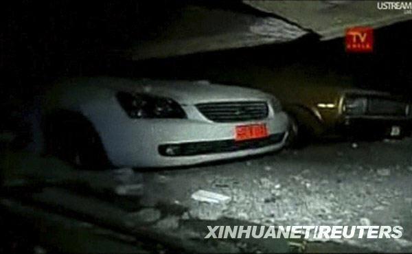 这张2月27日的视频截图显示,在智利首都圣地亚哥,汽车被压在因地震而垮塌的房屋下。