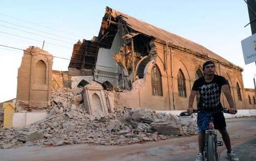 男子看着地震中受损的房屋
