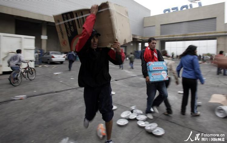 地震灾民搬运在超市内抢夺到的物资。