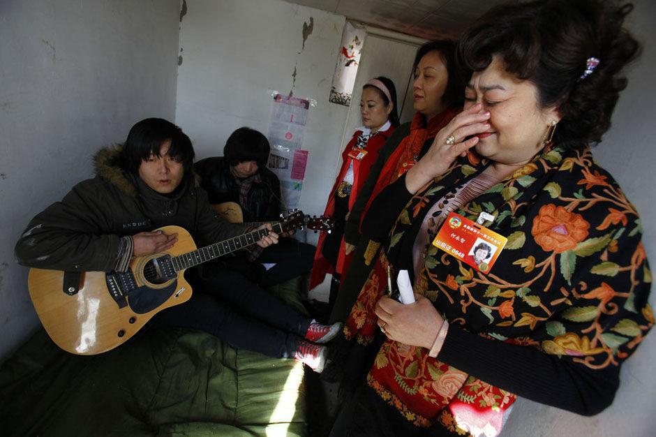 居住在唐家岭的李立国、白万龙坐在床上,演唱自己创作的《蚁族》,感动了前来看望的政协委员何永智、张礼慧、严琦。