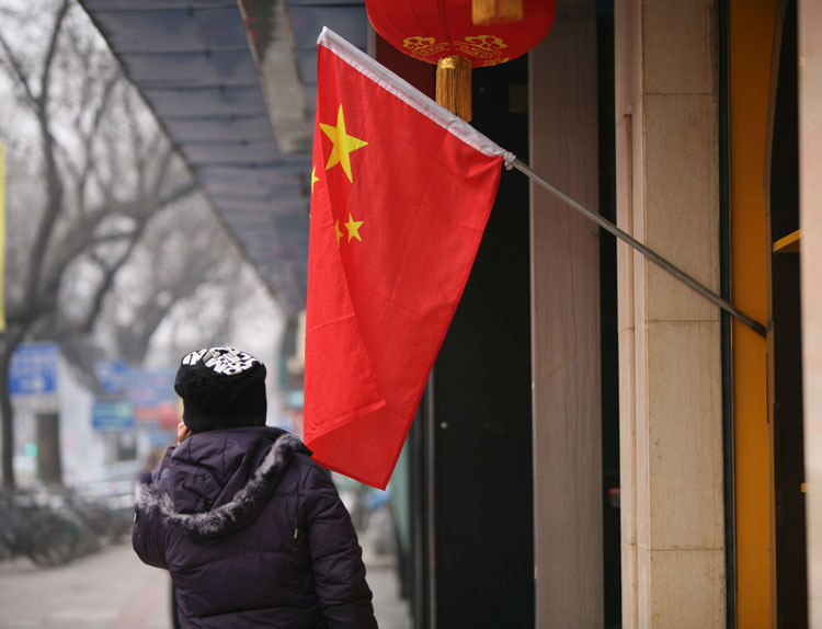 红旗下,一个老人正在打电话