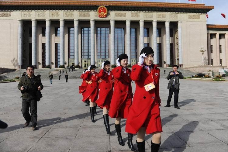 2010年3月5日,为两会提供服务的年轻姑娘在寒风中从人民大会堂前走过。