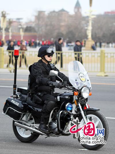 """2010年全国""""两会""""在北京隆重召开,为确保两会的顺利召开,北京市启动了一级安保为""""两会""""保驾护航,图为会场外值勤特警。中国网 杨佳摄影"""