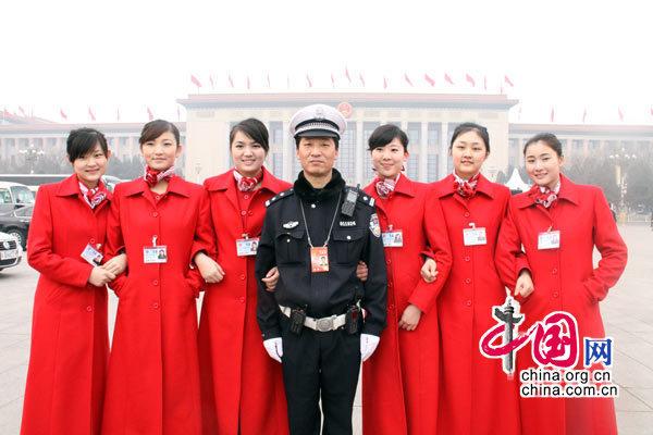 """每年""""两会"""",交警都是保障两会交通道路畅通必不可少的人物,平时严肃务实的警察叔叔也有可爱的一面。图为交警也被身着红装的少女吸引过来合个影。 (杨爱博摄)"""