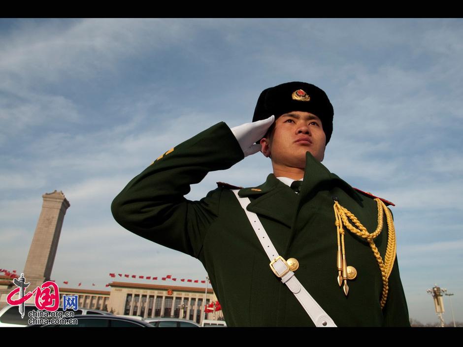 """全国""""两会""""安保方案日前启动,北京重点地区的警力全面升级,其中天安门地区、主会场外围、各代表驻地成为安保的重中之重。图为在天安门广场上执勤的武警战士。摄影 人民画报 段崴"""