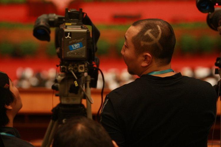 """2010年3月5日,第十一届全国人民代表大会第三次会议在北京人民大会堂开幕。一名外国电视媒体记者留着个性的""""镰刀斧头""""发型上会。"""