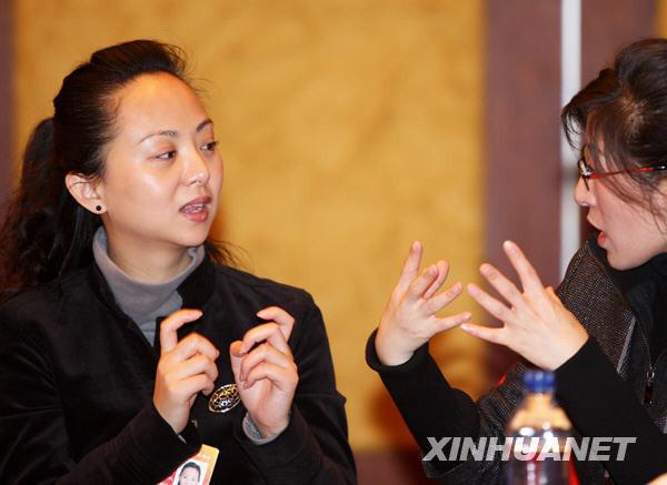 3月4日,一位手语翻译在政协文化艺术界小组会上为邰丽华委员(左)翻译与会委员的发言。(陈建力 摄)