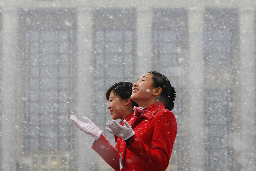 3月8日,北京降雪,两会服务人员享受雪趣。