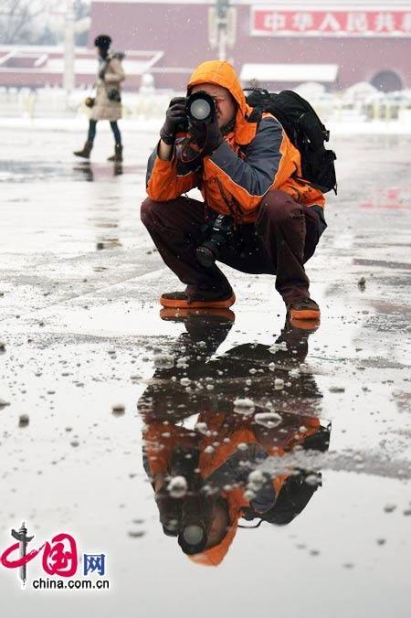 蹲在雪地上拍摄的记者 (杨佳摄)