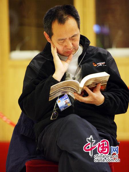 """参与""""两会""""报道的记者都要求提前很早通过安检进入会场,有些记者会随身携带一些消遣的读物,在紧张的会议未开始前享受阅读的乐趣。(胡迪摄)"""