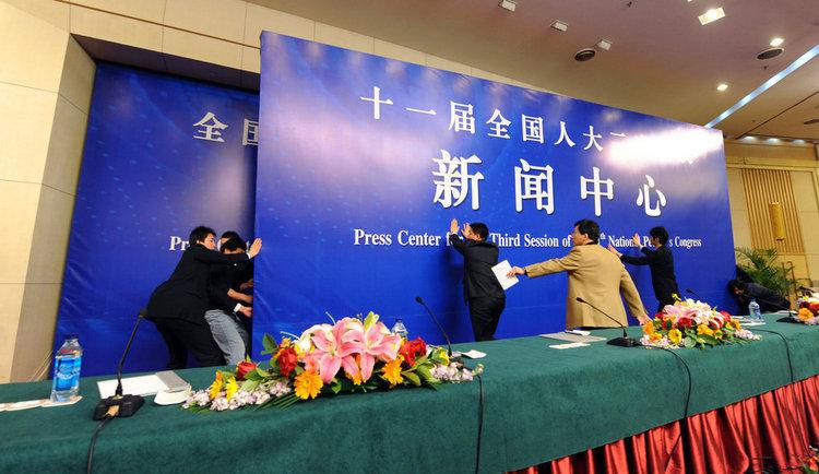 2010年3月11日,北京,两会新闻中心(梅地亚宾馆)多功能厅。工作人员在几分钟之内熟练的更换了会议背景板,为紧接着下一场集体采访做好准备。