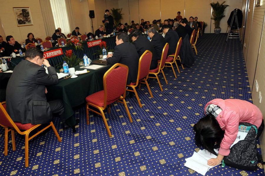 2010年3月4日,北京友谊宾馆,政协分组讨论会场,一名女记者一直跪在地上记录,离她不到两米的地方有一张空着的椅子。