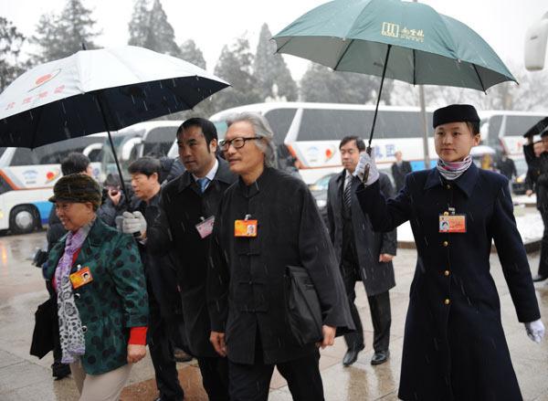 工作人员打着伞迎接代表
