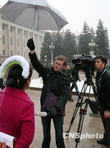 外国记者撑伞为代表挡风遮雪 (汤彦俊摄)
