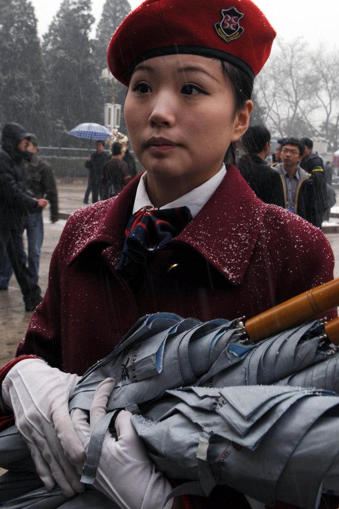 2010年3月14日,北京,十一届全国人大三次会议闭幕。图为大会堂外的服务人员在雪中抱伞等候。(CFP 版权所有 请勿转载)
