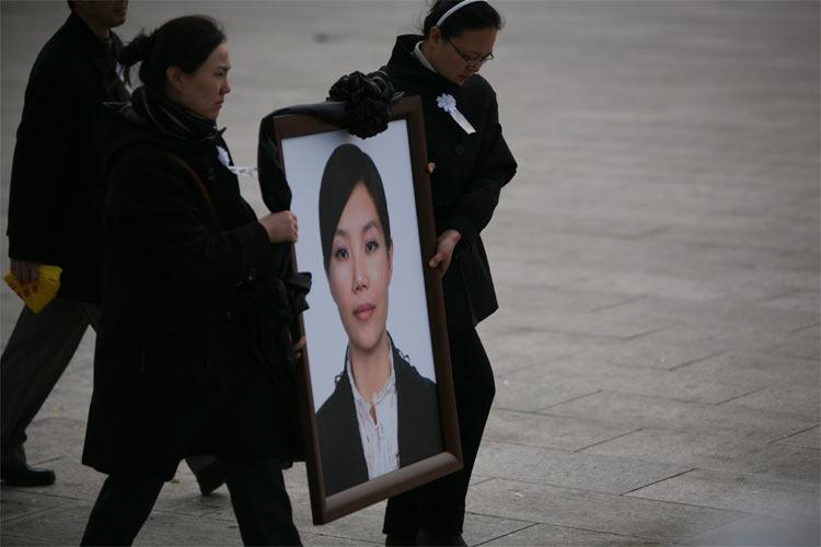 亲友抬着刘薇的遗像,离开追悼会现场