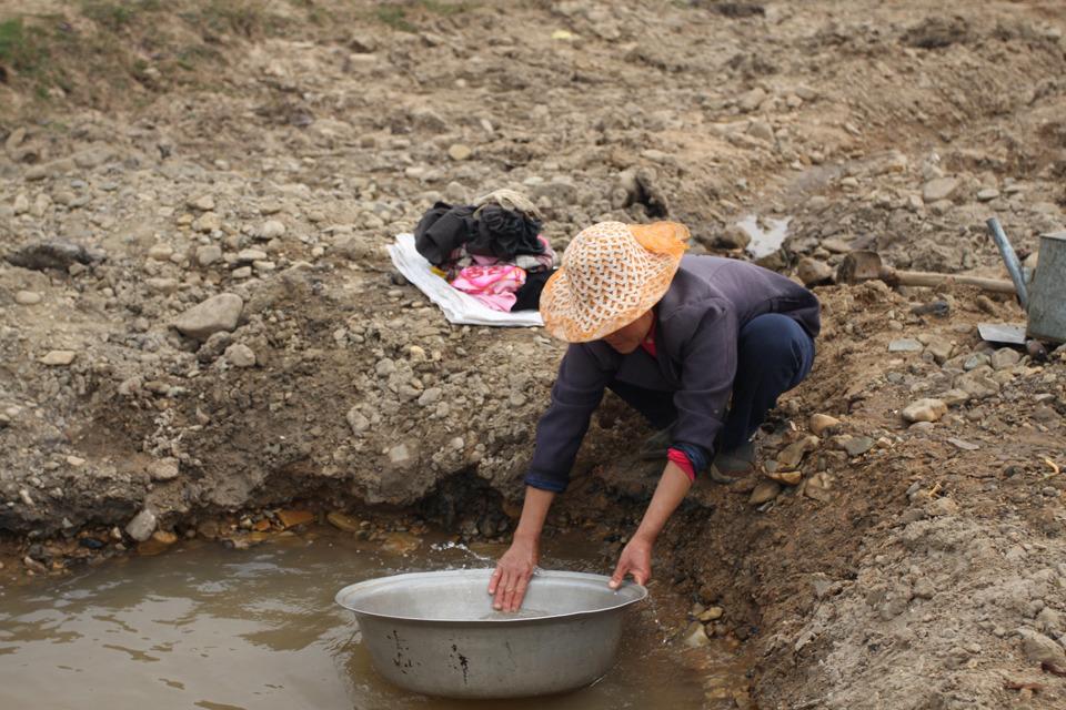 3月17日,云南曲靖市陆良县芳华镇。农民在挖出的坑里打水,这样的坑在这条干涸的河床有200多个。(摄:张蕾)