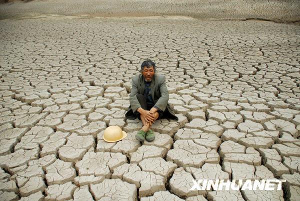 3月23日,一位老汉坐在罗平县九龙镇干涸的牛街河水库库底。新华社发(毛虹 摄)