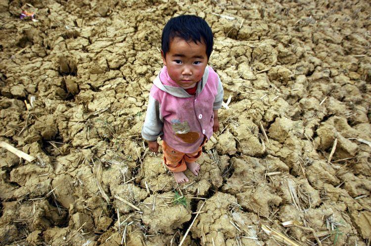 3月17日。广南县珠琳镇塘子边村。壮族小孩站在干裂的田地中。(都市时报 曲鸣飞/摄)