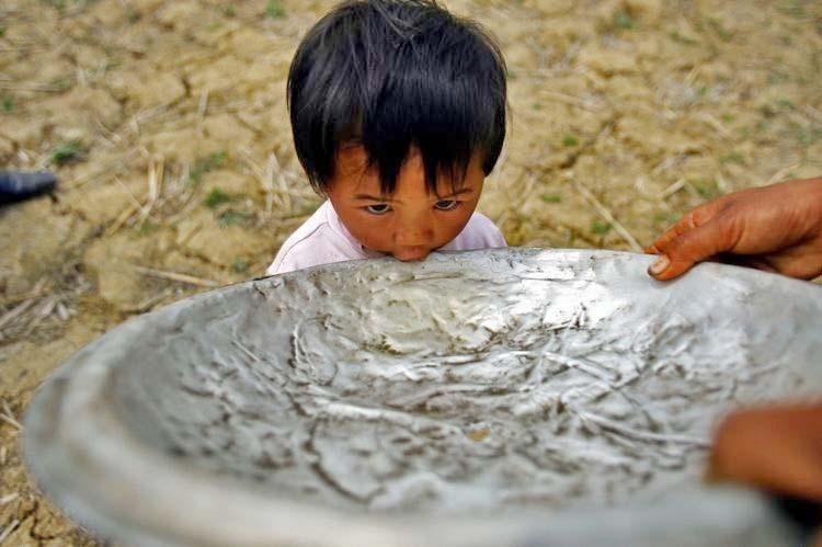 3月17日。广南县珠琳镇泥么冲村。田地边用锅盖喂小孩喝水。(都市时报 曲鸣飞/摄)
