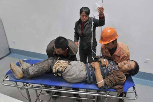 在医院内,两工友弯下腰,用双手把伤者移到担架车上 (记者 符光周/摄)