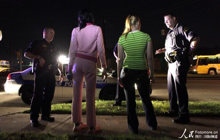 2009年11月4日,美国,达拉斯:警察同两名年轻女子交谈,这两名女子因卖淫罪被逮捕。