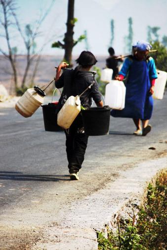 乡政府每天要为11个村头水,任务相当艰巨。离者坎村很远的很远的地方还能守候出一点水来,有劳力的村民家会派出人去,花上三个钟头守获一担水。图中的小姑娘就幸运地收获了一担水,但有遗憾---右图中空荡荡的塑料桶告诉我们她原本还想把它们也装上水挑回家的。贵州省贞丰县 饶顺林