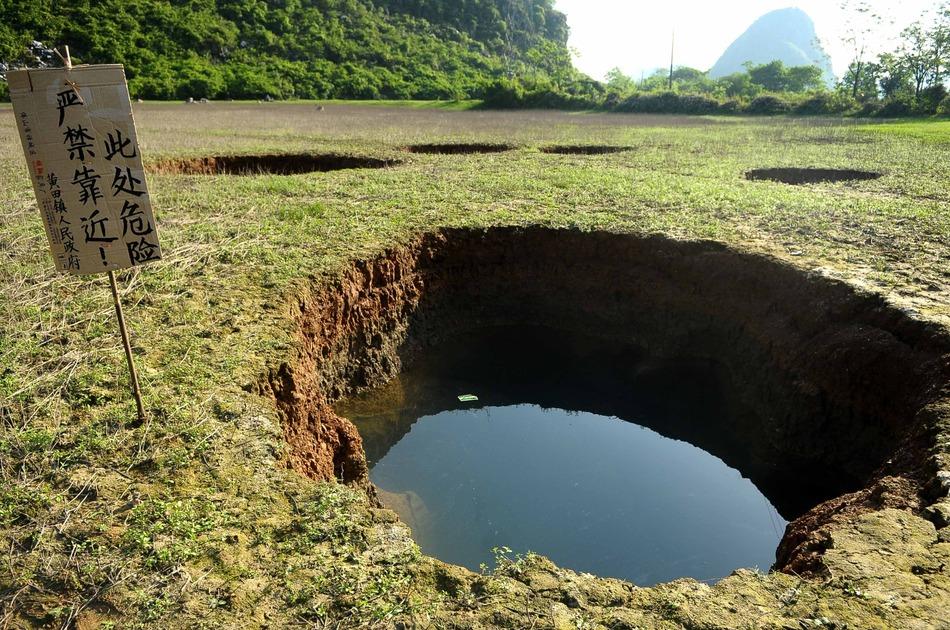 """4月8日在广西贺州一水塘拍摄的由地陷形成的的""""天坑""""。"""