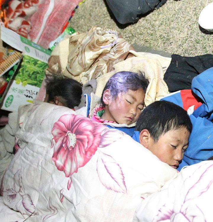 几名受灾儿童在露天睡觉