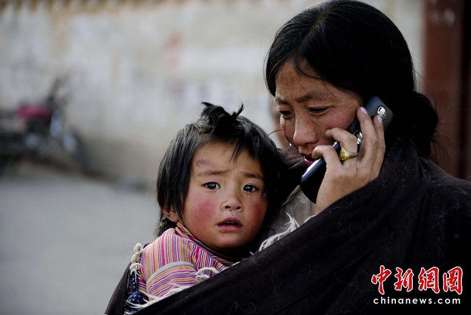 4月15日,青海玉树县体育场的地震灾民安置点内,一位母亲在与亲人通话时潸然泪下,怀里小女儿的脚伤还在等待医治。