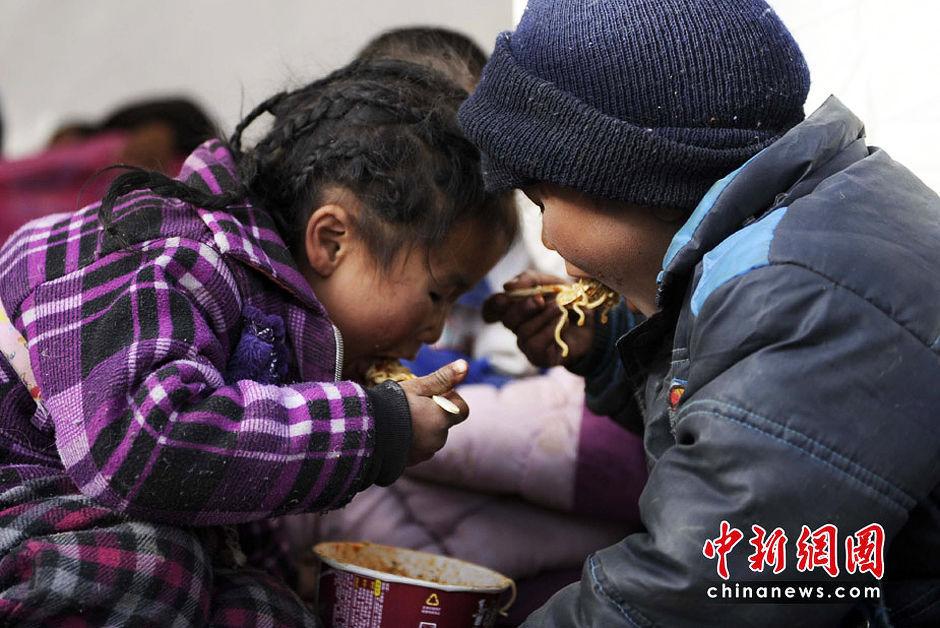 4月15日,青海玉树县体育场的地震灾民安置点,两名受灾孩童分食一盒方便面,一根不剩。(点击图片看下一篇)