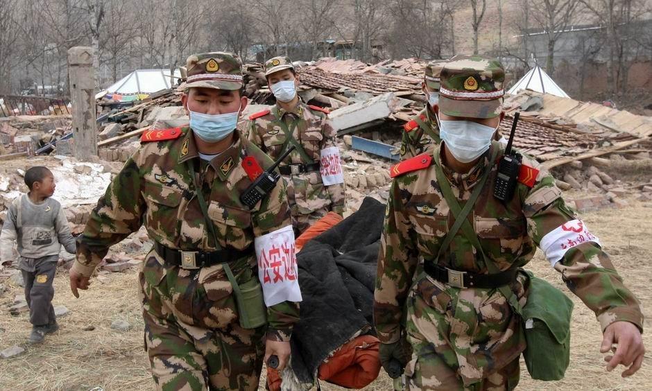 4月16日,公安边防部队医疗救护队员在将地震中受伤的群众转移到安全地带进行救治。