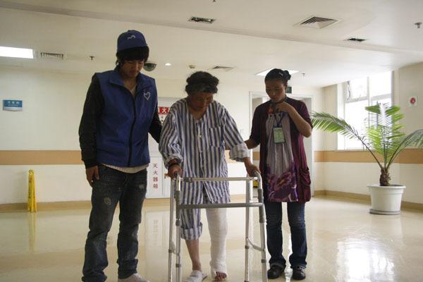 2010年4月21日成都华西医院,77岁藏族阿妈在志愿者的搀扶下到医院走廊活动。